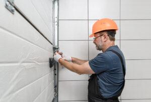 Worker installing garage door - Garage door services